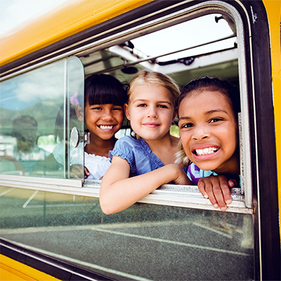 Smiling children looking out an open window on a school bus.