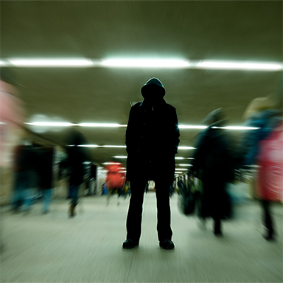 Hooded person standing in shadow while blurred people move past.